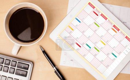 Photo pour Lieu de travail avec tablette pc affichage Calendrier et une tasse de café sur un close-up de table de travail en bois - image libre de droit