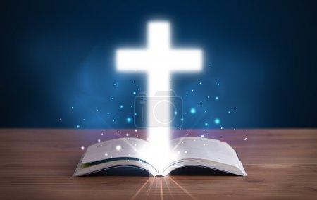 Photo pour Bible sainte ouverte avec croix rayonnante au milieu sur le pont en bois - image libre de droit