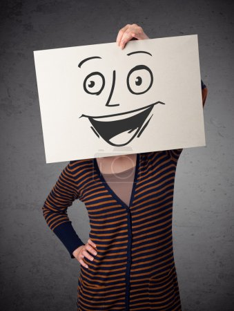 Photo for Young woman holding a cardboard with a smiley face on it in front of her head - Royalty Free Image