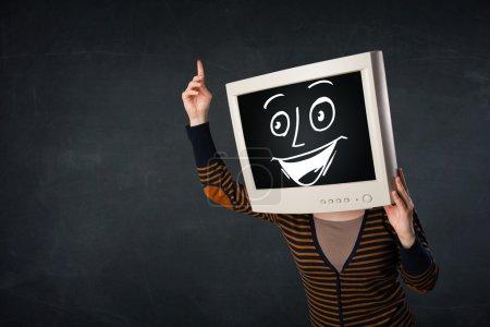 Photo pour Fille avec un écran visage moniteur et un visage de dessin animé heureux - image libre de droit
