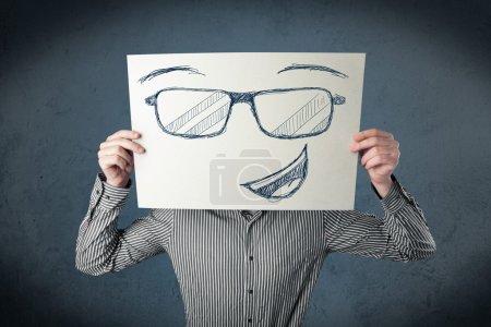 Foto de Joven empresario sosteniendo un papel con la cara sonriente delante de su cabeza - Imagen libre de derechos