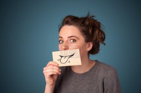 Photo pour Jolie jeune fille tenant carte blanche avec sourire dessin sur fond dégradé - image libre de droit