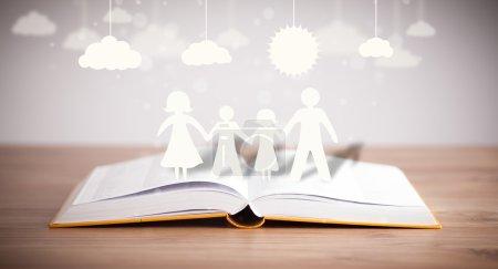 Photo pour Figures en carton de la famille sur le livre ouvert. Le symbole de l'unité et du bonheur - image libre de droit