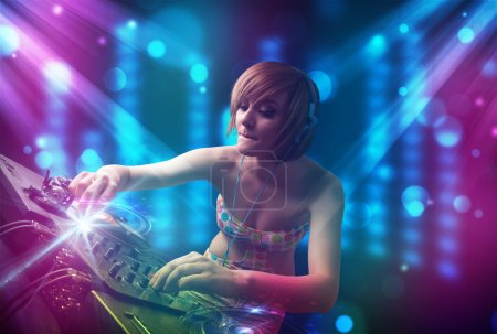 Photo pour Jolie dj mélanger de la musique dans un club avec des lumières bleus et violets - image libre de droit
