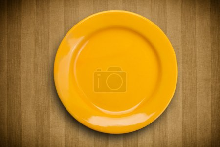 Photo for Colorful empty shiny plate on grungy background table - Royalty Free Image
