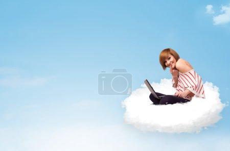 Photo pour Jolie jeune femme avec ordinateur portable assis sur un nuage avec un espace vide - image libre de droit