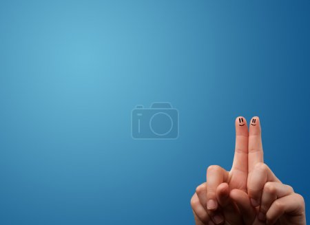 Photo for Happy smiley face fingers cheerfully looking at empty blue background copy space - Royalty Free Image