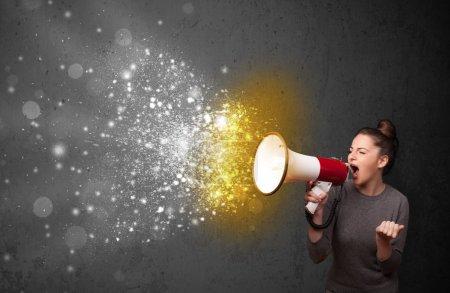 Photo pour Femme criant en mégaphone et particules d'énergie brillante explosent concept - image libre de droit