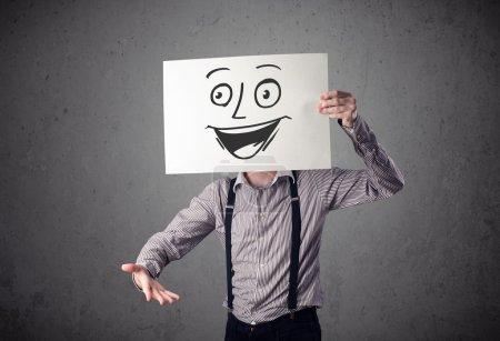 Photo pour Jeune homme d'affaires tenant un carton avec un visage souriant devant sa tête - image libre de droit