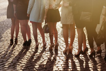 Photo for A row of young pretty women on high heels standing on block paving - Royalty Free Image