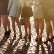 A row of young pretty women on high heels standing...