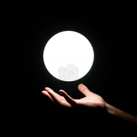 Foto de Bola de luz brillante por la mano humana aislada sobre fondo negro - Imagen libre de derechos