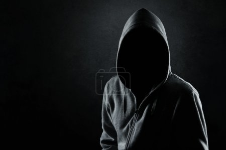 Photo for Silhouette of hooded man or hooligan over dark, concrete background - Royalty Free Image