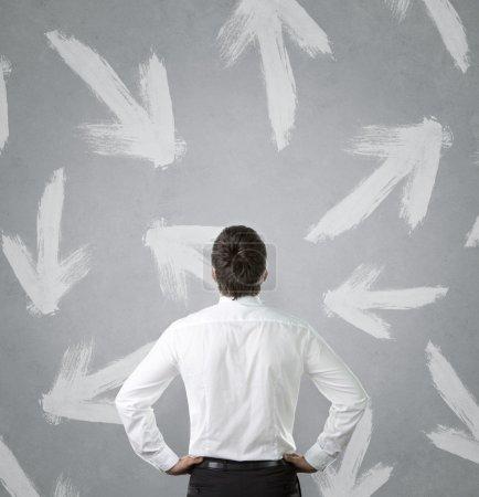 Photo pour Jeune homme d'affaires en regardant plusieurs flèches pointée dans différentes directions - image libre de droit