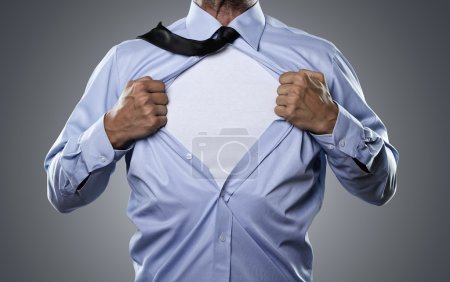 Photo for Young businessman tearing his shirt off isolated on gray background with copy space - Royalty Free Image