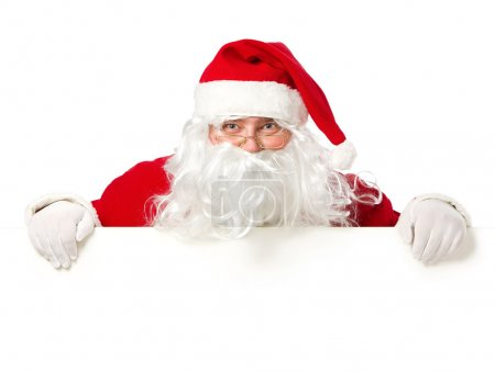 Photo for Happy Santa Claus looking out from behind the blank sign isolated on white background with copy psace - Royalty Free Image