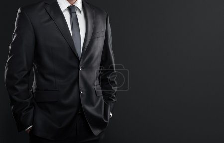 Photo for Close up of businessman in suit over dark gray background with copy space - Royalty Free Image