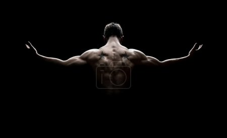 Photo for Rear view of healthy young man with his arms stretched out isolated on black background - Royalty Free Image