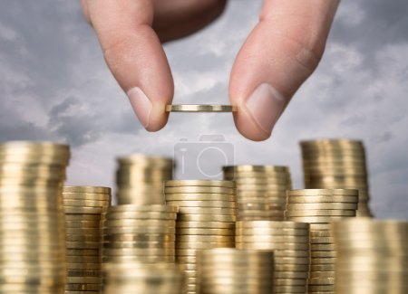 Photo for Savings, close up of male hand stacking golden coins over sky background - Royalty Free Image