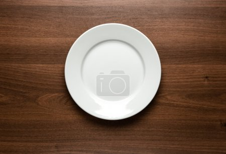 Photo for Close up of white empty plate at the wooden table with copy space - Royalty Free Image