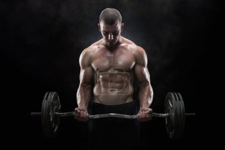 Photo for Close up of young muscular man lifting weights over dark background - Royalty Free Image