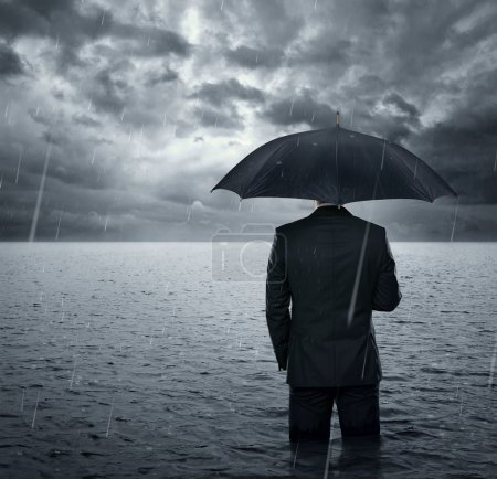 Photo for Businessman standing in the dramatic ocean before storm - Royalty Free Image