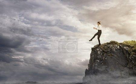 Photo pour Jeune femme d'affaires marchant sur le bord de la falaise - image libre de droit