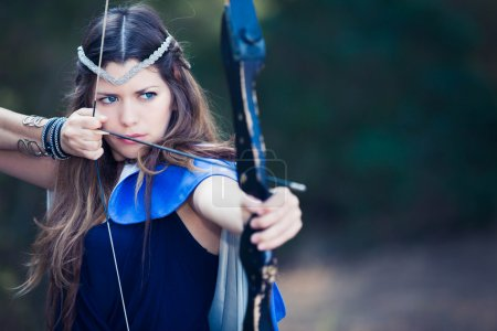 Photo for Fictional forest hunter girl with bow and arrow - Royalty Free Image