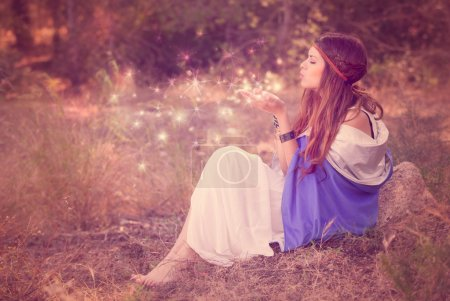 woman blowing wishes in forest. fairy or elf
