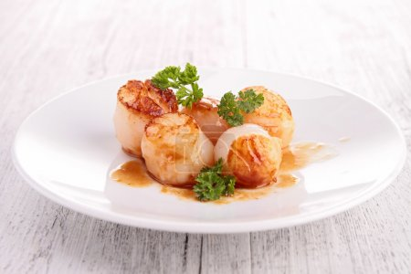 Photo for Seared scallops on plate, on wooden table - Royalty Free Image