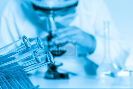 Laboratory assistant working with a microscope in lab