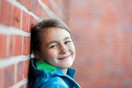 Portrait of   little cute girl next to Brick Wall
