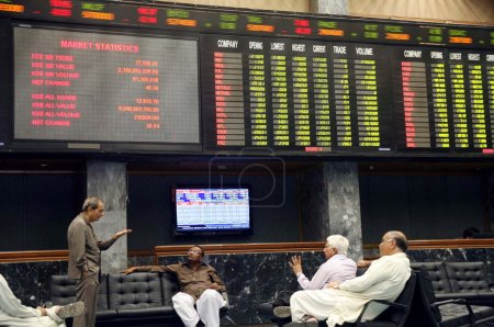 Stockbrokers sit near an index board showing a sharp rise in stocks during trading session at Karachi Stock Exchange