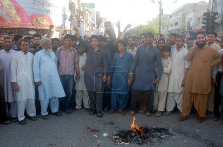 Traders burn tyres as they are protesting against killing of a shopkeeper by extortion mafia, during a demonstration at Tariq Road