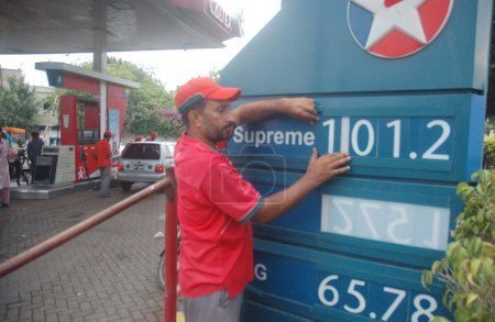 Fuel station employee displays new prices of petroleum products at a fuel station in Karachi