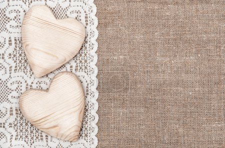 Burlap background with lacy cloth and wooden hearts