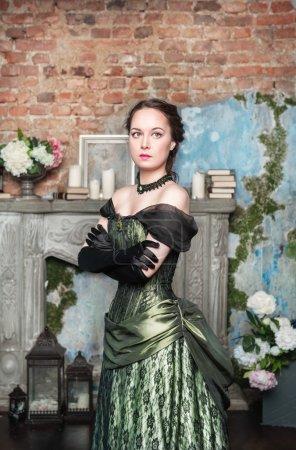 Photo pour Belle jeune femme en robe médiévale longue près de la cheminée - image libre de droit