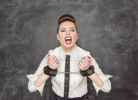 Screaming business woman with handcuffs on the bla...