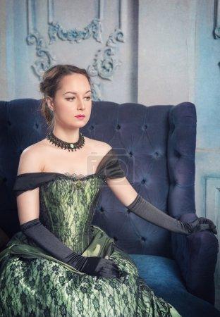 Photo pour Belle jeune femme en robe médiévale verte sur le canapé - image libre de droit