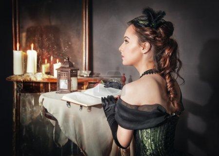 Photo pour Belle jeune femme en robe médiévale verte assise près du miroir - image libre de droit