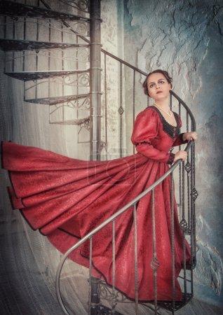 Photo pour Belle jeune femme en rouge flottant robe médiévale sur l'escalier - image libre de droit