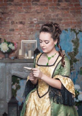 Photo pour Belle jeune femme en robe médiévale verte lecture lettre - image libre de droit