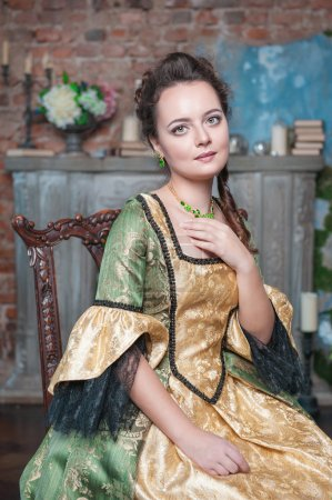 Beautiful woman in medieval dress on the chair