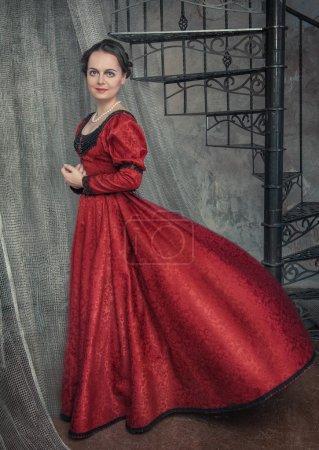 Photo pour Belle jeune femme en robe médiévale flottante rouge - image libre de droit