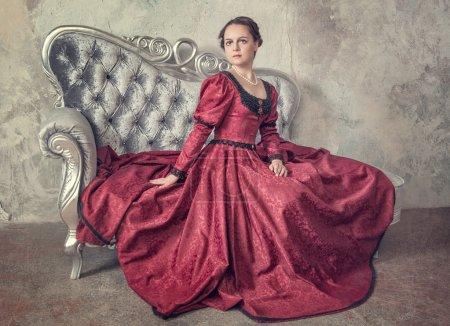 Photo pour Belle jeune femme en robe médiévale rouge sur le canapé - image libre de droit