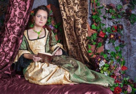 Photo pour Belle jeune femme en vert robe médiévale livre de lecture - image libre de droit