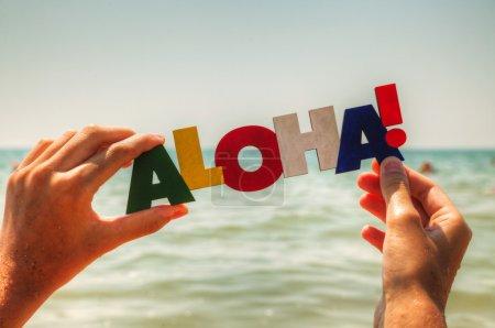 Photo pour Main de femme tenant le mot coloré 'Aloha' sur fond bleu - image libre de droit
