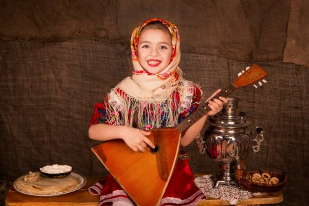 Photo for Beautiful russian girl in a shawl playing balalaika - Royalty Free Image