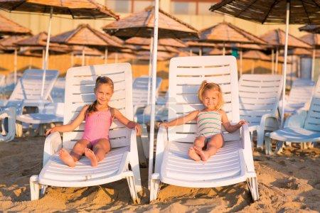 Two adorable kids sunbathing on a beach