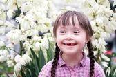 Porträt von schönen jungen Mädchen auf Blumen Hintergrund